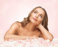 有玫瑰花瓣的美丽的妇女 图库摄影
