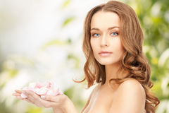 有玫瑰花瓣的美丽的妇女 免版税图库摄影