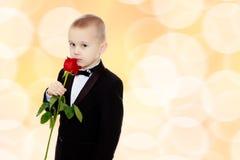 有玫瑰花的小男孩 免版税图库摄影