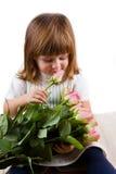有玫瑰花的美丽的小女孩 免版税库存照片