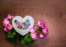 有玫瑰装饰花束的手工制造心形箱子在木背景的 库存图片