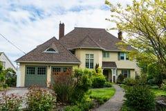 有环境美化的中产阶级黄色房子在前院 库存图片