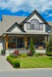 有环境美化的郊区房子在前面和天空蔚蓝背景 库存图片