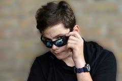 有现代太阳镜的十几岁的男孩 库存照片