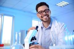 有现代显微镜的男性科学家在化学实验室 免版税库存照片