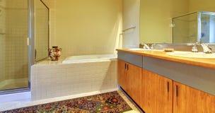 有现代木机柜、木盆和阵雨的卫生间。 图库摄影