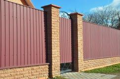 有现代样式设计的门的金属篱芭从街道边的 免版税图库摄影