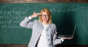 有现代膝上型计算机举行枪姿态的教育家聪明的聪明的夫人在她的顶头黑板背景 疲倦的老师懊恼 免版税库存图片