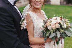 有现代花束和时髦的柔和新郎hugg的华美的新娘 免版税库存照片