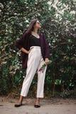 有现代首饰和时兴的神色的时髦的漂泊女孩 摆在晴朗的庭院里 愉快的有花束的boho无忧无虑的女孩  免版税库存图片