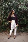 有现代首饰和时兴的神色的时髦的漂泊女孩 摆在晴朗的庭院里 愉快的有花束的boho无忧无虑的女孩  免版税库存照片