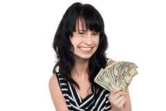 有现金的微笑的俏丽的女孩 免版税图库摄影