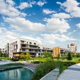 有现代公寓单元的公开绿色公园和蓝天 库存图片