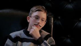 有玻璃和一根稀薄的髭的一年轻人在一个黑皮椅坐 一个聪明的人握他的手在他的下巴并且考虑 股票录像