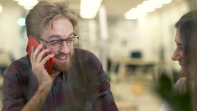 有玻璃和偶然格子衬衫的有胡子的微笑的人谈话在坐与女孩的手机在桌上 影视素材
