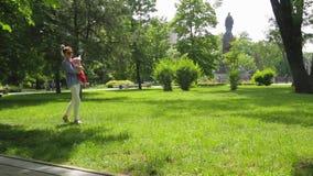 有玻璃和她逗人喜爱的女婴步行的年轻母亲在绿色草甸