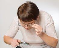 有玻璃和放大镜的年长妇女 免版税库存图片