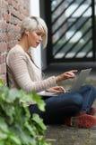 有玻璃和片剂的美丽的白肤金发的妇女 免版税库存照片