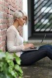 有玻璃和片剂的美丽的白肤金发的妇女 免版税库存图片