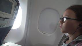 有玻璃和耳机的女孩观看在显示器的录影被修造入在飞机的客舱的扶手椅子 影视素材
