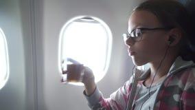 有玻璃和耳机的女孩观看在显示器的录影被修造入扶手椅子和饮用的汁液在客舱 股票录像