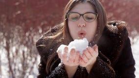 有玻璃和貂皮皮大衣的愉快的女孩膨胀从她的手的雪 影视素材