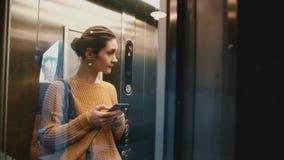 有玻璃墙的年轻愉快的妇女骑马电梯,门打开,并且她走微笑使用智能手机购物的app 股票视频