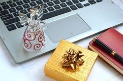 有玻璃天使和一个黄色金黄礼物盒的便携式计算机 图库摄影