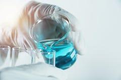 有玻璃实验室化工试管的研究员有液体的 免版税库存照片