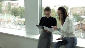 有玻璃工作在商业中心和身分的谈论两个年轻企业的女孩在窗口工作 股票视频
