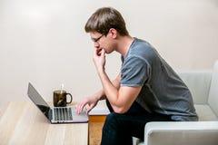 有玻璃工作的被集中的年轻人在一台膝上型计算机在一个家庭办公室 沉思地扫描在显示的文本 侧视图 图库摄影