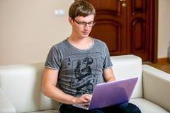 有玻璃工作的被集中的年轻人在一台膝上型计算机在一个家庭办公室 键入在键盘和纸卷文本在显示 库存图片