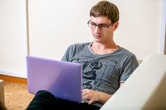 有玻璃工作的被集中的年轻人在一台膝上型计算机在一个家庭办公室 在键盘和扫描的印刷品在显示的文本 库存图片