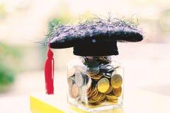 有玻璃瓶子的方形的学术盖帽在再书的硬币 库存照片