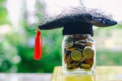 有玻璃瓶子的方形的学术盖帽在再书的硬币 免版税库存照片