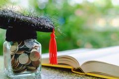 有玻璃瓶子的方形的学术盖帽硬币和被打开的书o 免版税库存照片