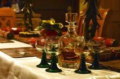 有玻璃的威士忌酒蒸馏瓶在一张欢乐地装饰的桌上 库存图片
