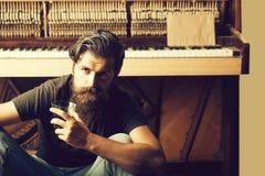 有玻璃的有胡子的人在木钢琴附近 免版税库存图片