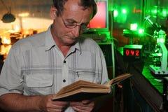 有玻璃的科学家在他的实验室读了书 免版税库存照片
