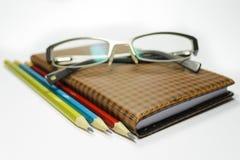 有玻璃的笔记本和铅笔 免版税库存图片