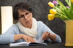 有玻璃看书的深色的资深妇女 免版税库存照片