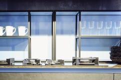 有玻璃门和照明设备的厨房现代碗柜 现代内部的厨房 免版税库存图片