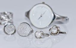 有珍珠的银色耳环在手表背景  免版税库存照片