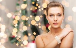有珍珠耳环和镯子的美丽的妇女 库存图片