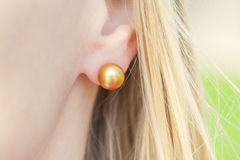 有珍珠耳环的妇女的耳朵 免版税库存照片