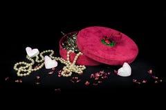 有珍珠项链和甜心的红色节日礼物箱子 库存图片
