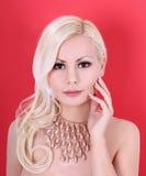有珍珠项链的美丽的白肤金发的女孩在红色 库存图片