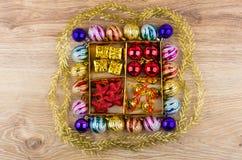 有球、星和响铃的,圣诞节球Goldish箱子 免版税库存图片