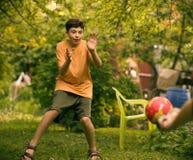 有球关闭的少年男孩踢橄榄球的照片 图库摄影
