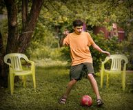 有球关闭的少年男孩踢橄榄球的照片 库存图片
